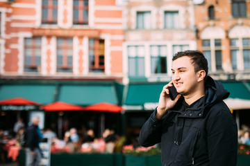 Young handsome man on the street speaking on the phone