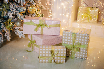 Gifts under the tree in gold, pink and beige tones