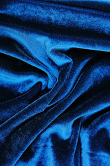 Silk dress material cloth texture pattern. Tailoring stitching concept. Shiny beautiful fashion fabric. Shiny clothing material sample.Creased fabric. Blue velvet.