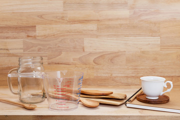 measuring cup and wooden spoon, cooking supplies on wood background