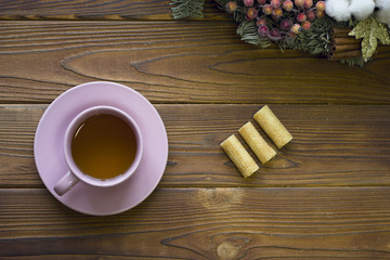 Pink tea cup, cookies and pine twigs on a rustic wooden background, top view