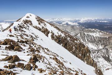 Two skiers on mountain peak, Mammoth Lakes, California, USA