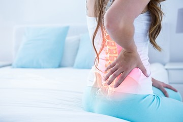 Digital composite of highlighted spine of woman with back pain