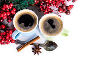 Cups of fragrant coffee on a Christmas background of fir branches, berries and cones