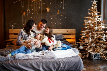 A family of four hugging in front of the christmas tree on the bed with candles and gifts. New year's eve. Cozy holiday at the fir-tree. love, happiness and big family concept