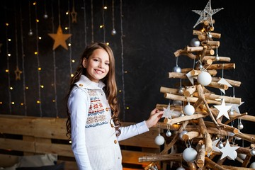 A brunette gilr decorating  christmas tree. A surprised girl. A girl dreaming. New year's eve. Cozy holiday at the unusual wooden christmas tree with lights and decorations.