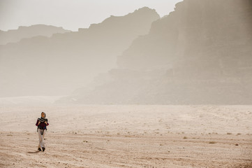 Woman hiking through desert scenery, Wadi Rum, Jordan, Middle East