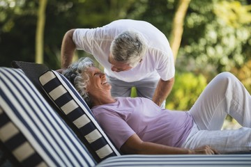 Senior man bending over woman resting on lounge chair