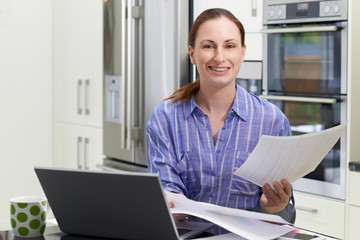 Female Freelance Worker Using Laptop In Kitchen At Home