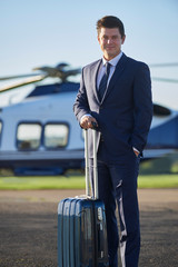 Portrait Of Businessman Standing In Front Of Helicopter