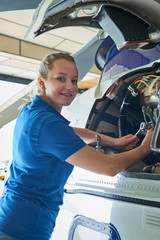 Portrait Of Female Aero Engineer Working On Helicopter In Hangar