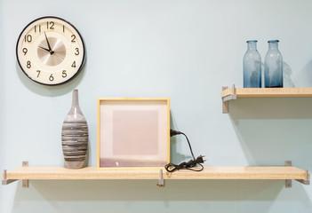 Vintage home decor: wood shelves with frame, vase, houseplants, clock on wooden board, retro home interior.