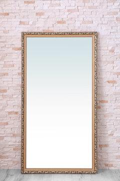 Beautiful big mirror near brick wall