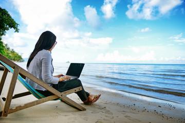 Business woman using a laptop beside the beach