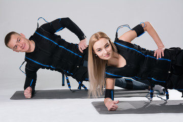 Young man and a woman in an electric muscular suit are trained to stimulate themselves