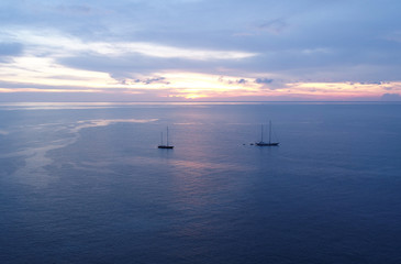 Aerial view of beautiful sunset over the sea with sailing boats