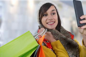 Young happy woman with shopping bags, taking selfie