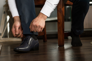 groom business man putting on smart shoes for wedding