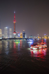 Tourboat on Huangpu river with city skyline at night, Shanghai, China