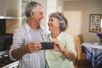 Cheerful senior couple with mobile phone in kitchen