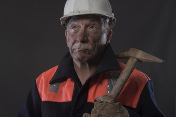 Mature miner covered in coal dust holding a pick axe