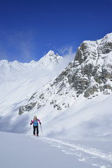 Female back-country skier ascending to Piz Laschadurella, Piz Nuna in background, Sesvenna Alps, Engadin, Graubuenden, Switzerland