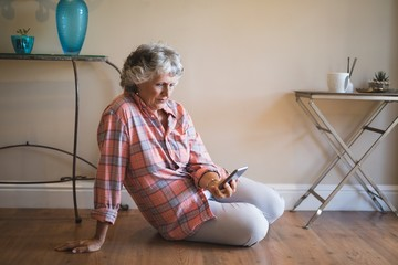 Senior woman watching mobile phone while sitting on floor