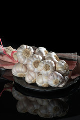 String of french pink garlic on old tin plate on black background