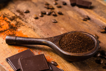 Dark roasted pure arabica coffee beans and ground coffe on the wooden table, copy space