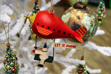 Christmas robot riding red blimp with Let it Snow sign on white fluffy Christmas tree with other ornaments