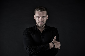 Macho in black shirt pose with folded hands