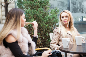 Female girl friends in the city relaxing at cafe terrace in worm autumn. Friendship and quality time