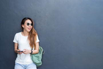 Outdoor lifestyle portrait of pretty sexy young asian girl in travel and glasses style on gray wall background. Asian woman texting message on phone. Copyspace available. Lifestyle and technology.
