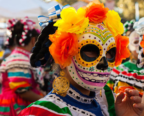 Portrait of girl wearing colorful skull mask and paper flowers for Dia de Los Muertos/Day of the Dead celebration