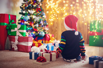Boy and sitting on the floor with presents near christmas tree