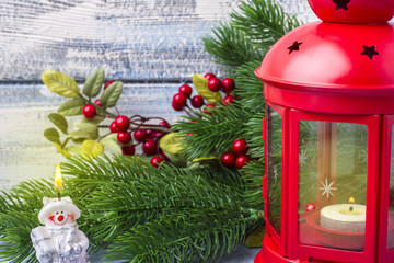 Red candlestick with a candle inside and a branch of a Christmas tree. Theme of the New Year and Christmas