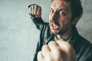 Aggressive man punching with fist, victim's pov