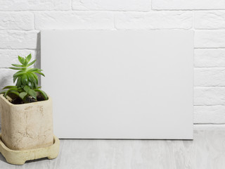 Mockup poster. White empty canvas. Brick wall on background.