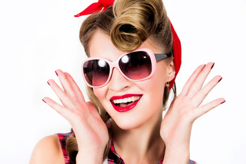Happy girl in pin-up style wearing sunglasses on white background