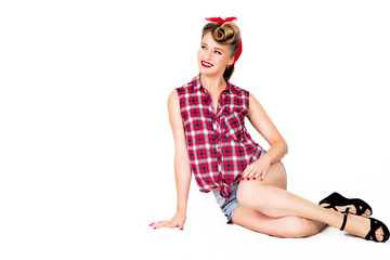 Sexy pin-up girl in shorts and high heels sitting on a floor over white background. Beauty, fashion. Full length portrait.