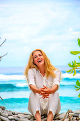 Blonde woman is sitting on the beach