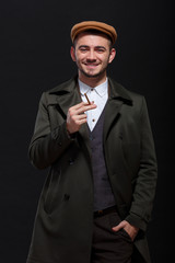 A man with a cigarette in his hand and a hand in his pocket on a black background