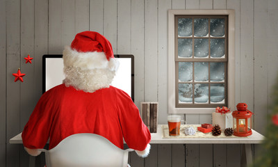 Christmas evening in Santa Claus room. Santa work on his computer. Snow and cold weather can be seen through the window.
