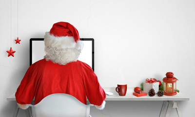 Santa Claus work on computer. Christmas decorations beside with free space on the wall for text.