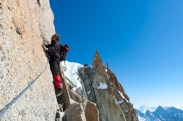 Foto op Plexiglas Alpinisme Climbing in Chamonix. Climber on the stone wall of Aiguille du Midi