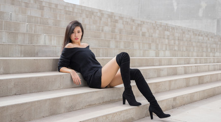Beautiful Asian woman sitting on steps outside