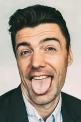 Young Caucasian businessman showing tongue