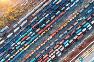 Top view of colorful cargo trains. Aerial view from flying drone of colorful freight trains on the railway station. Wagons with goods on railroad. Heavy industry. Industrial conceptual scene. Vintage