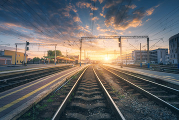 Foto op Canvas Treinstation Railway station and beautiful colorful sky at sunset. Industrial landscape with railroad, blue sky with red and orange clouds in dusk. Railway junction in the evening. Railway platfform.Transportation
