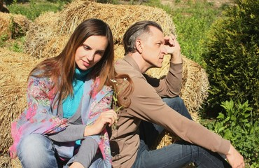 A loving happy young couple in the background of a haystack. Summer country walk.